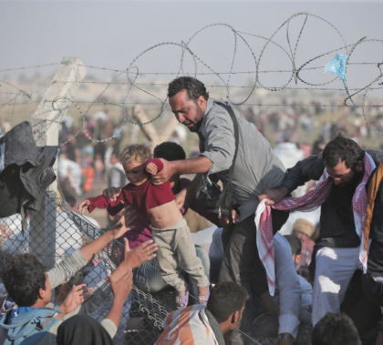 A Syrian refugee hands a baby over the broken border fence into Turkey 2015. AP