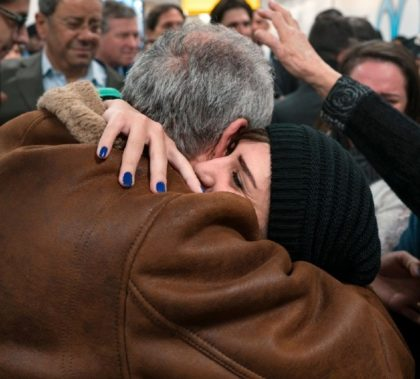 Travelers arriving from Syria embrace family members at John F. Kennedy International Airport in New York City (AP Photo/Craig Ruttle)