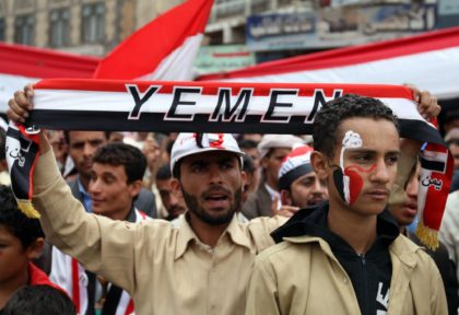 Yemeni students hold the flag of their country as they protest the war. (Arabic Fars News)